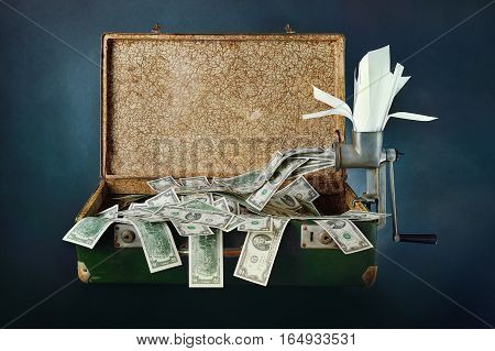 Old green suitcase with money on a blue background