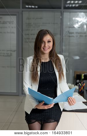 Portrait Of Confident Young Businesswoman Holding File In Office.