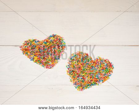 Candy sprinkles form heart shape. Multicolored heart-shape from candy confetti on white wooden background. Valentines day concept. Copyspace.