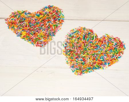 Candy sprinkles form heart shape. Multicolored heart-shape from candy confetti on white wooden background. Valentines day concept
