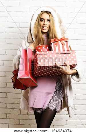 young fashionable sexy pretty woman or girl with long blonde hair in waist coat of white fur with hood and fashion makeup holding red big presents or gifts with pegs on brick wall studio background