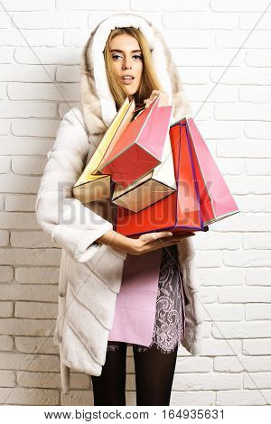 young fashionable sexy pretty woman or girl with long beautiful blonde hair in pink dress waist coat of white fur with hood and fashion makeup holding colorful package on brick wall studio background