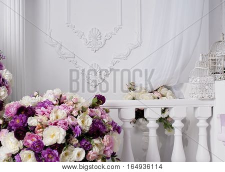 lush bouquet of roses near decorative balcony and wall with modeling