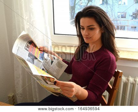 Brunette girl reading a newspaper at home near the window