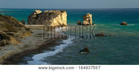 Aphrodite stones in sea and gravel beach (Cyprus). Tourist spot. Panoramic view.