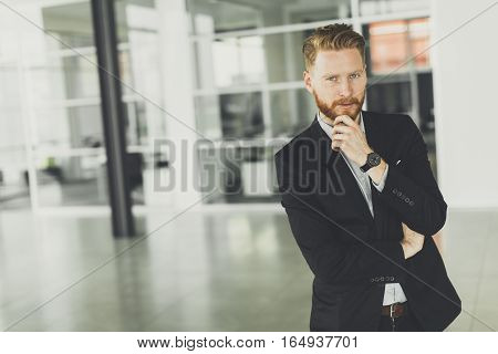 Modern redhair man posing in the office
