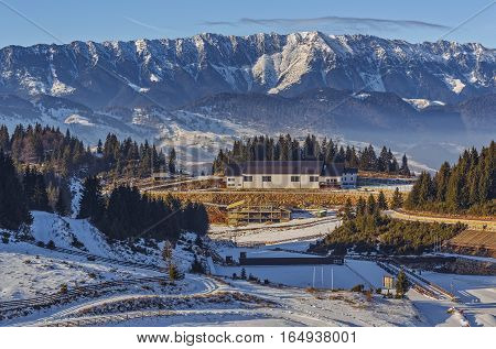Panoramic view over the touristic ski resort Cheile Gradistei Fundata and the majestic snowy Piatra Craiului mountains range Romania.