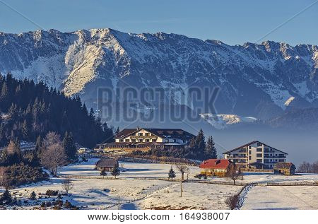 Sunny winter scenery with majestic snowy Piatra Craiului mountains chalet or lodging buildings in Cheile Gradistei Fundata touristic resort Romania. Idyllic quiet holiday retreat destinations.
