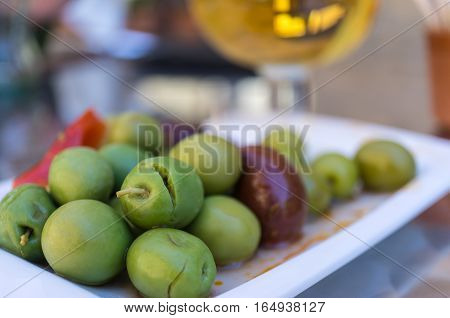 Close-up of Spiced olives in a small plate on the tapas bar table a typical Spanish black and green split olive. In the background a blurred beer