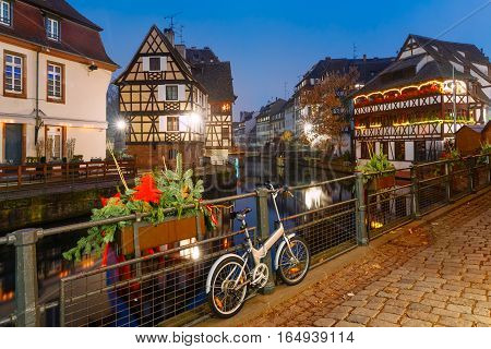 Traditional Alsatian half-timbered houses with mirror reflections in Petite France during twilight blue hour decorated and illuminated at christmas time, Strasbourg, Alsace, France