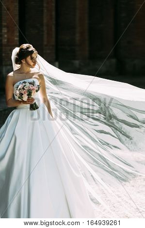 Lovely bride in white dress on the windy weather