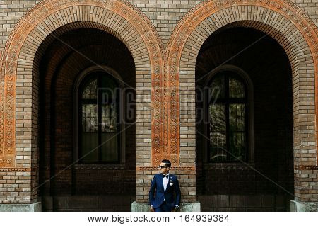 Groom in the sunglasses stands next to the arch