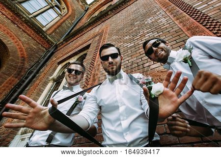 Stylish groomsmen in the sunglasses and bow-ties