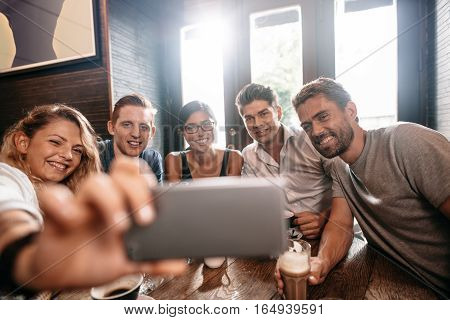 Diverse group of friends taking selfie on smart phone. Young men and women sitting at cafe table and taking a self portrait on cell phone.