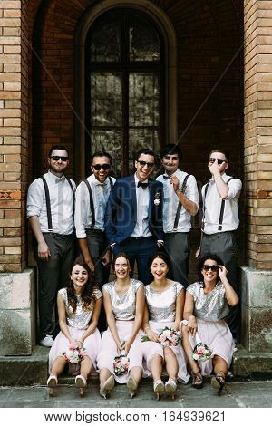 Groomsmen with a groom and bridesmaids are smiling