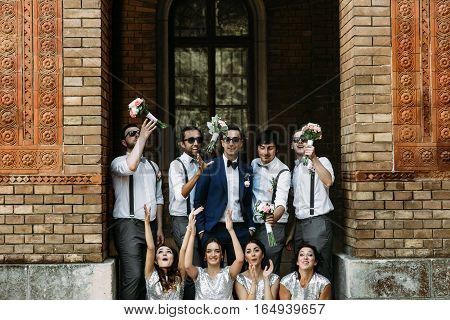 Bridesmaids are playing with their bouquets on the street