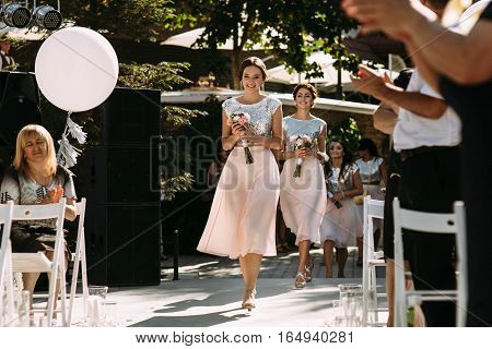 Joyful bridesmaids are walking on the wedding ceremony
