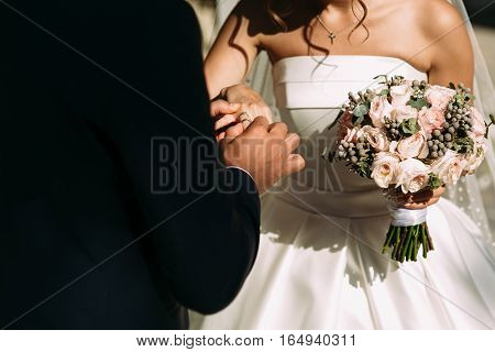 Wedding ring on the bride's finger n the ceremony