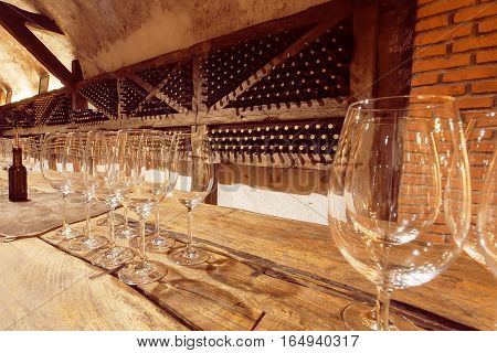 KVARELI, GEORGIA - OCT 3, 2016: Wine glasses on wooden table of the tasting room of old cellar Khareba Winery on October 3, 2016. The cellar tunnel was opened in 1962 for the World Wine Congress