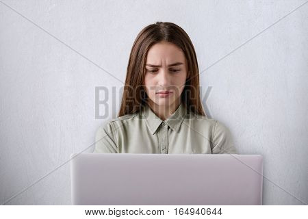 A portrait of displeased beautiful girl having tired expression working with her laptop isolated over grey background. A student having wry face being tired of working at computer and studying