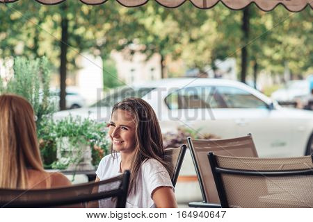 Attractive young brunette woman talking to a friend while sitting outside at a cafe table
