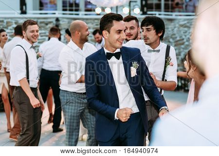 Groom is dancing funny with his friends