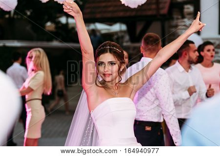 Bride with the hands up on the dance floor