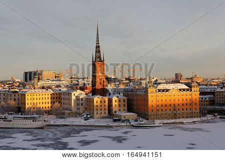 STOCKHOLM - JAN 08 2017: Old beautiful buildings at Riddarholmen lit with warm light a cold winter morning ice on the sea. January 08 2017 in Stockholm Sweden