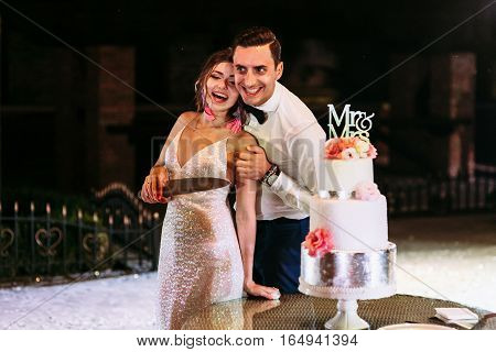Joyful just married couple next to the wedding cake