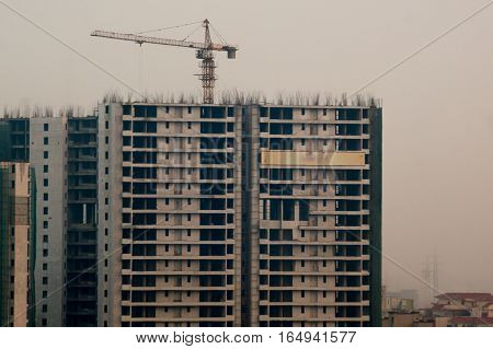 Under construction buildings with a crane and concrete structure in Noida Delhi Gurgaon. The surge in people living in these cities has led to huge construction projects