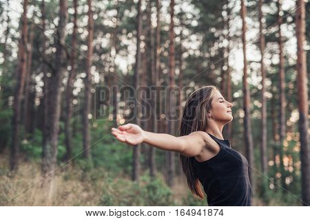 Attractive young brunette woman standing among trees in a forest with her eyes closed and arms raised up to embrace nature