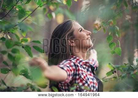 Attractive young brunette woman smilng while standing among leaves and branches in a forest with arms raised up to embrace ature