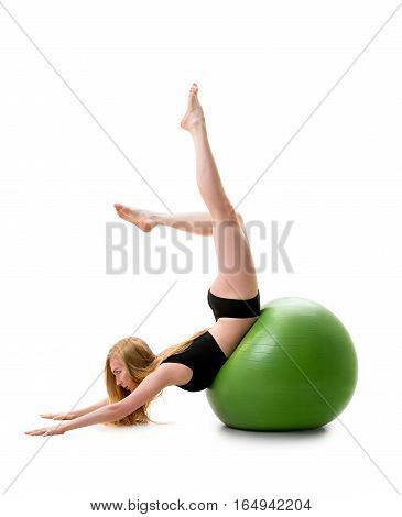 Long haired blonde in black shorts and briefs lying on her stomack on green big fitball posing in studio with her legs streching up