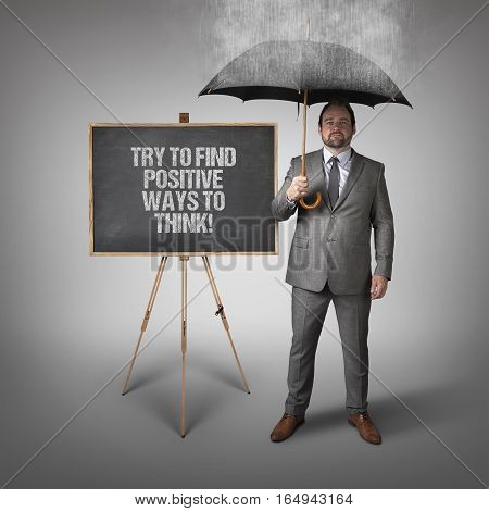 Try to find positive ways to think  text on blackboard with businessman and umbrella