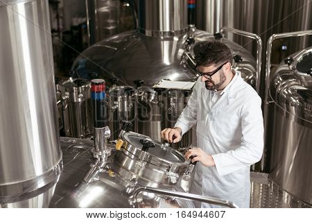 Important technologies. Satisfied young handsome man using computer at beer factory while working and controlling the process.