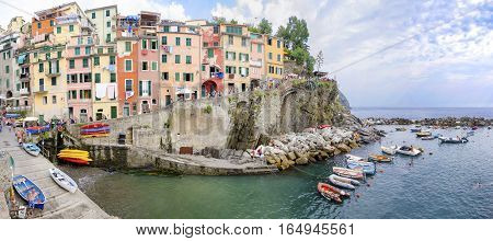 Riomaggiore village La Spezia province Liguria northern Italy. Panoramic view of the colourful houses on steep hills sea rocks beach laundry on balconies boats and tourists. Part of the Cinque Terre National Park and a UNESCO World Heritage Site.