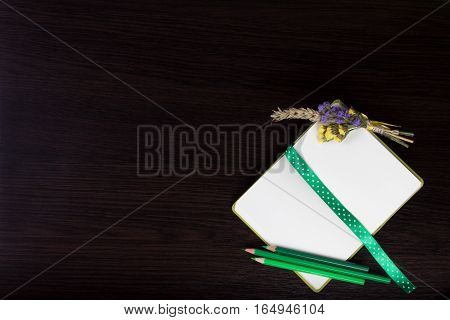 Open notebook with polka dot ribbon as a bookmark, boutonniere and green pencils in the corner of dark wooden background. Top view. Flat lay. Can be used as a field for text input, notebook cover.