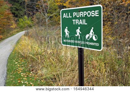 All purpose trail sign alongside a park path meandering through autumn foliage in Cleveland, Ohio, the United States.