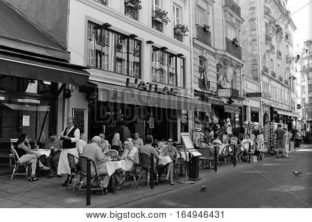 Black and white photo of active Parisian outdoor cafe and street in June 2016.