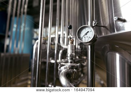 Control important process. Measuring gauge and pipes being used in brewery.