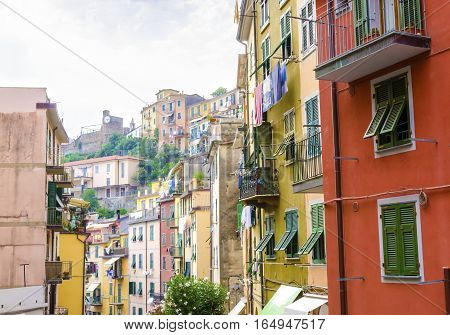 Riomaggiore village La Spezia province Liguria northern Italy. View of the colourful houses on steep hills the castle with clock laundry on balconies. Part of the Cinque Terre National Park and a UNESCO World Heritage Site.