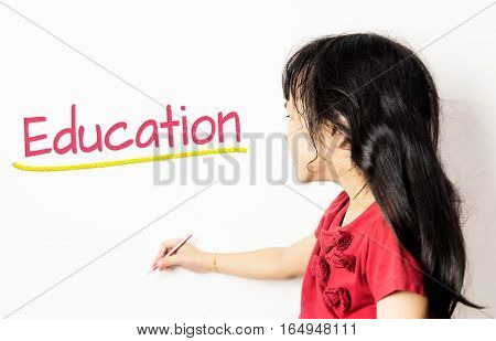 Asian Kid wrote Education on a white board.