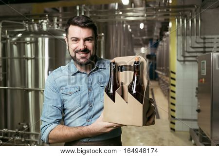 Happy brewer. Delighted young handsome man holding bottles of alcohol while standing in brewery and smiling.