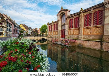Quay, decorated with flowers. Summer day in the city of Colmar. France.