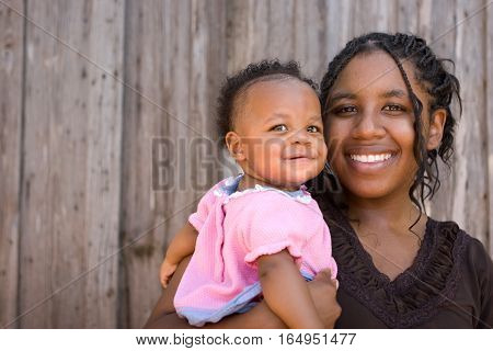 Teenage African American mother holding her daughter.