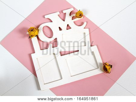 Frame for photo with letter wooden fishing on a pink and white background. Dried buds with yellow roses