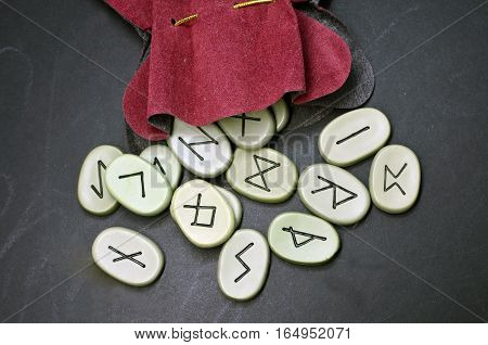 runes for fortunetelling on a black wooden Board