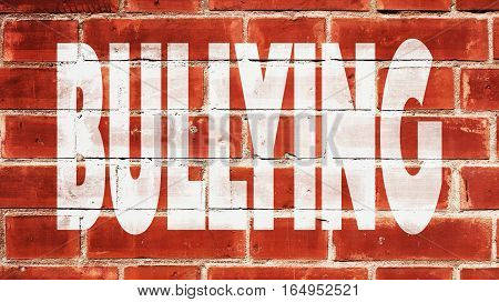 Bullying Written On A Red Brick Wall.