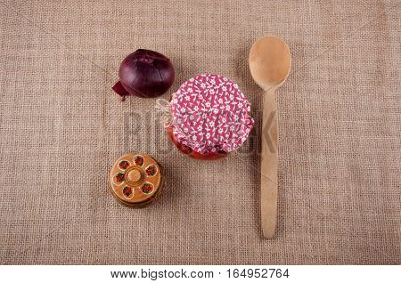 Authentic Still Life. Red onion wooden box with pattern spoon and jar covered by red cloth lay on sackcloth as background. Top view