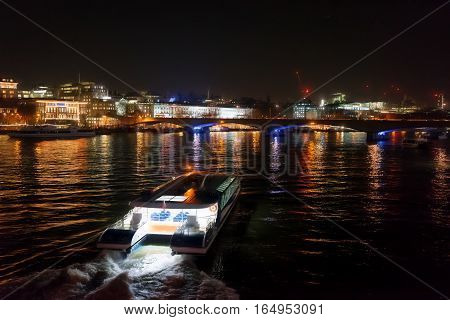River Thames capture at night with a ferry boat service linking other destinations along the River in central London.